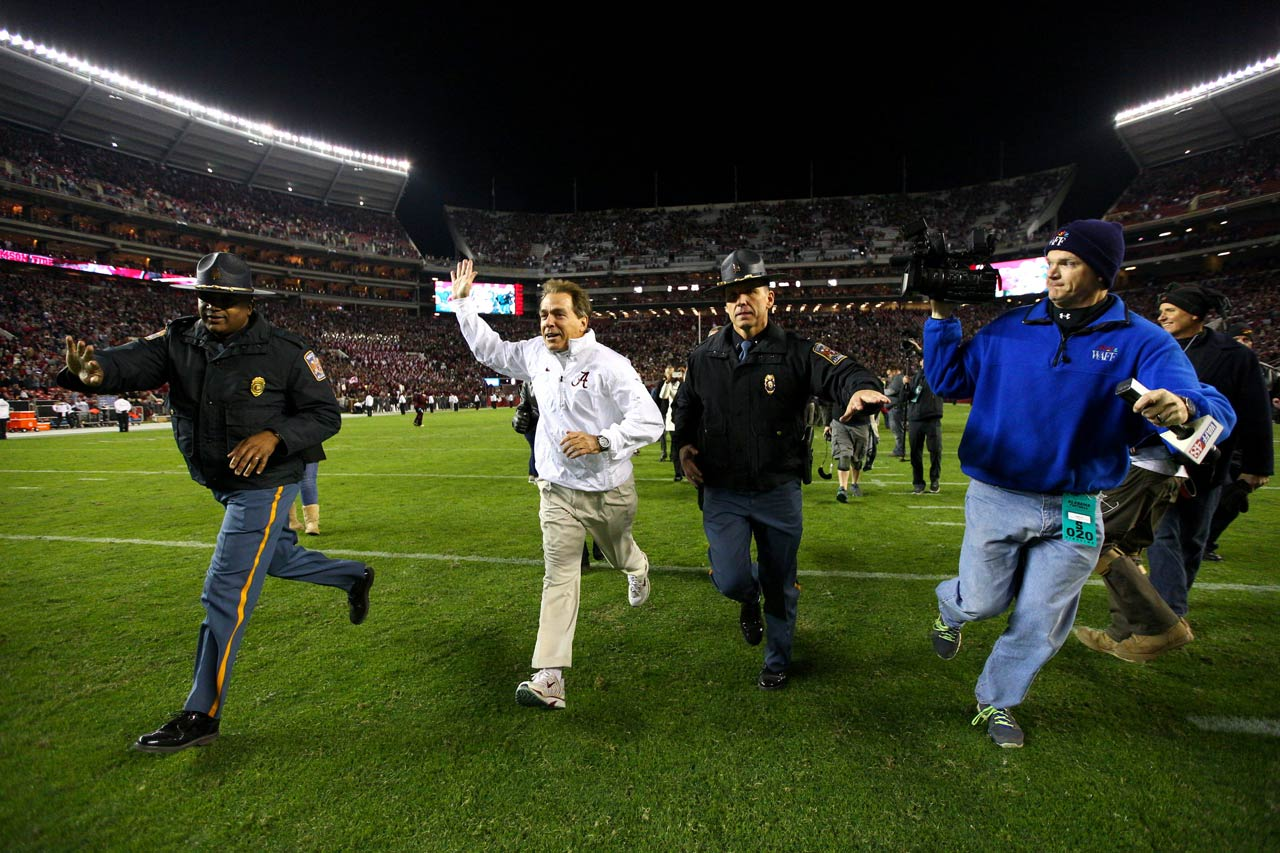 Alabama head coach Nick Saban waves as he runs off of the field after the Crimson Tide won 25-20 over Mississippi State.