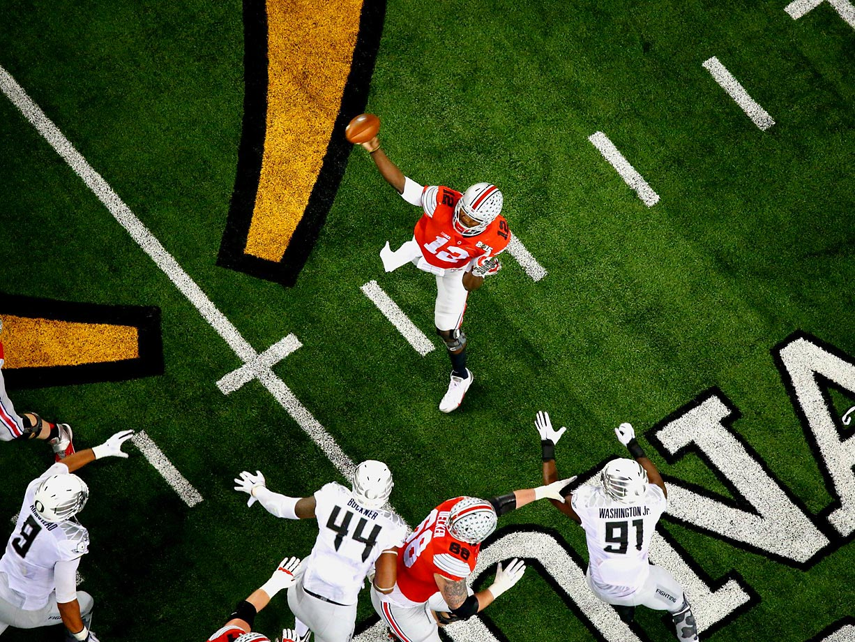 Ohio State quarterback Cardale Jones prepares to throw in the face of three Oregon defensive linemen. Jones completed 16 of his 23 passes during the Buckeyes' 42-20 win.