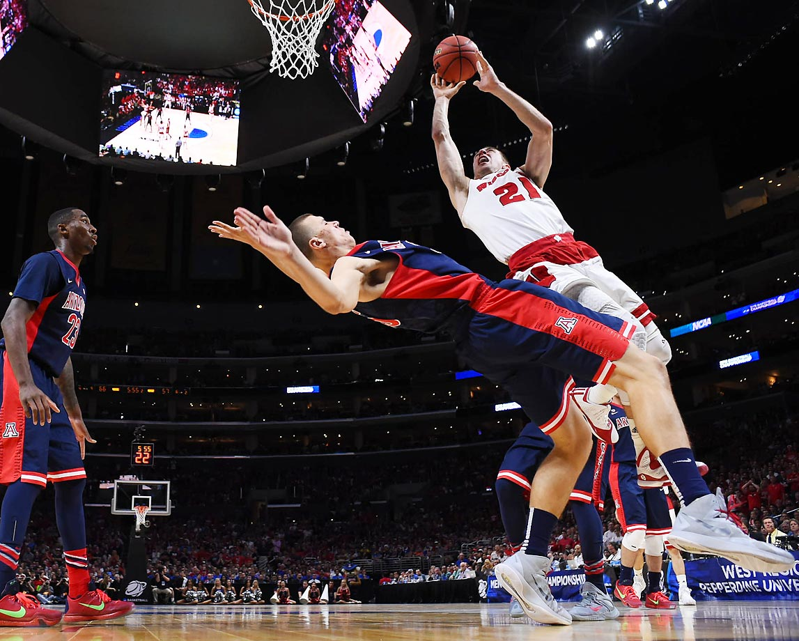 Wisconsin Badgers guard Josh Gasser barrels into an Arizona defender during the teams' Elite 8 matchup in Los Angeles. Wisconsin prevailed 85-78 to earn a date with Kentucky in the Final Four.