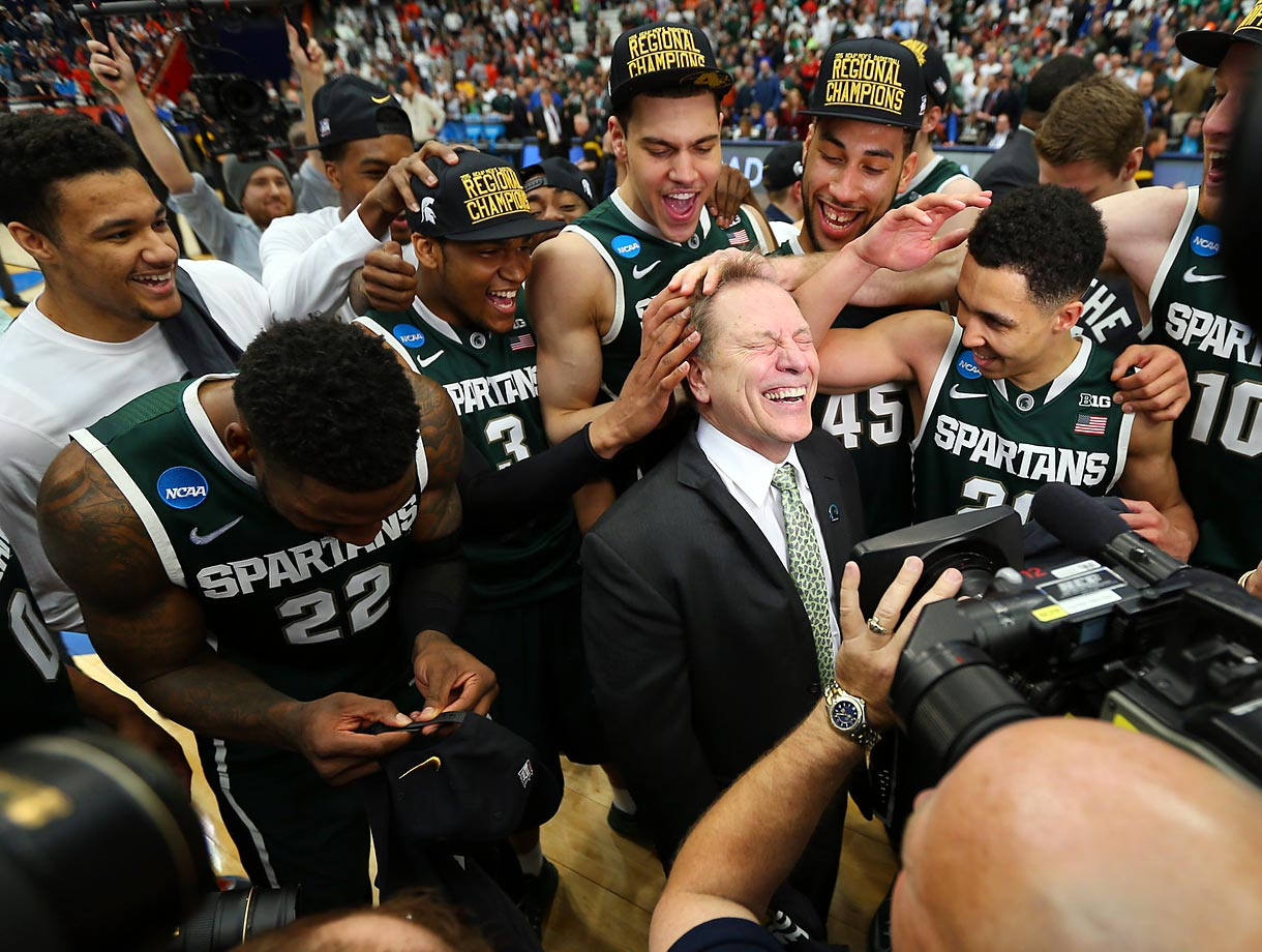 Michigan State players celebrate their Final Four appearance with coach Tom Izzo, who has reached the Final Four seven times in 21 seasons as Spartans headman.
