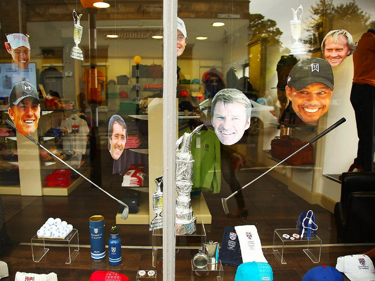 Cutouts of golfers' heads in a window of a store near the British Open.