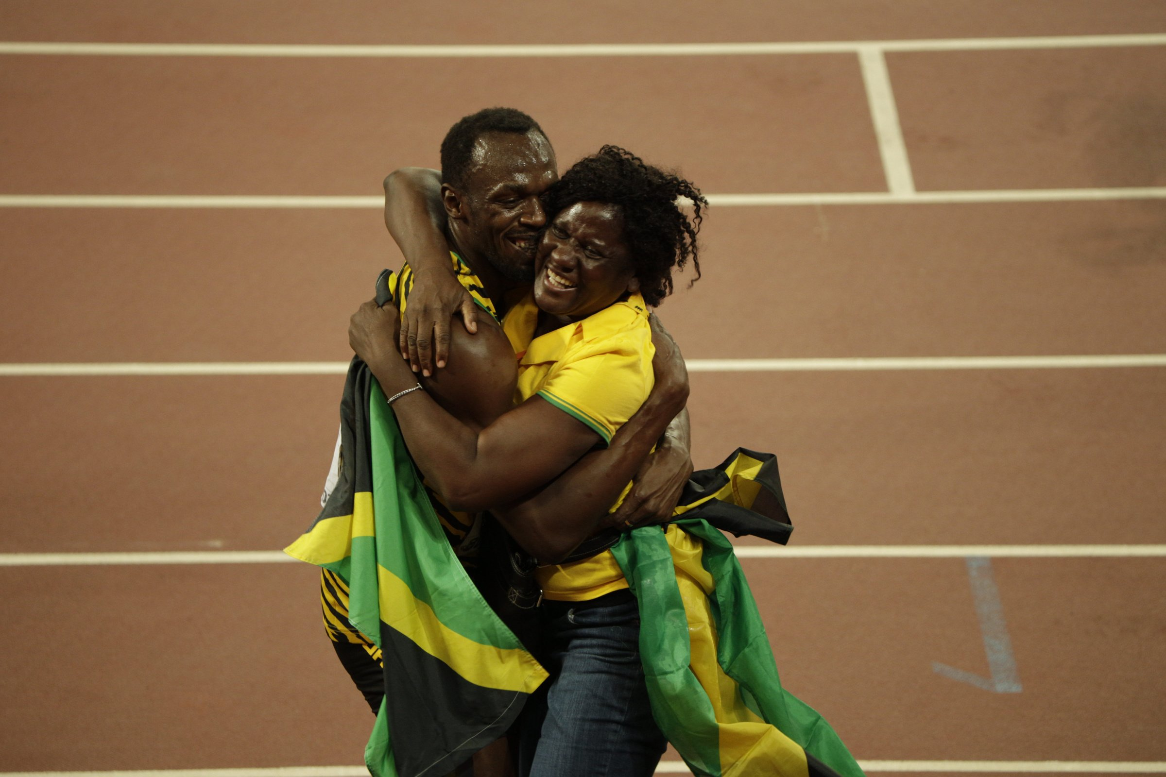 Usain Bolt (JAM) celebrates with his mother, Jennifer, after his 100-meter victory.