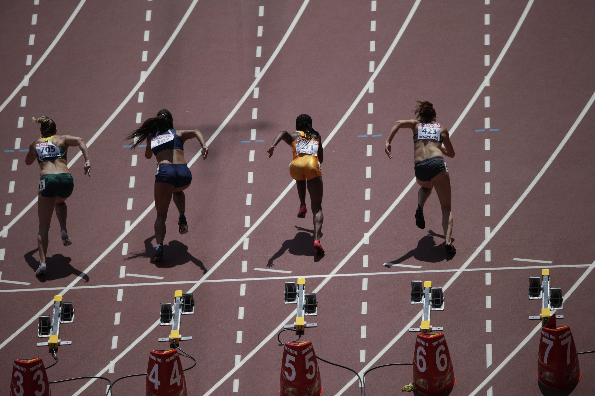 Athletes in the first section of the women's 100-meter dash start.