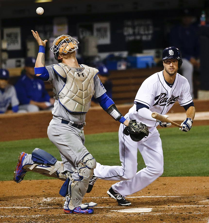 Yasmani Grandal of the Los Angeles Dodgers tries to palm a bunt attempt by Colin Rea of the Padres.  Grandal missed the catch but after Rea was called out on strikes.