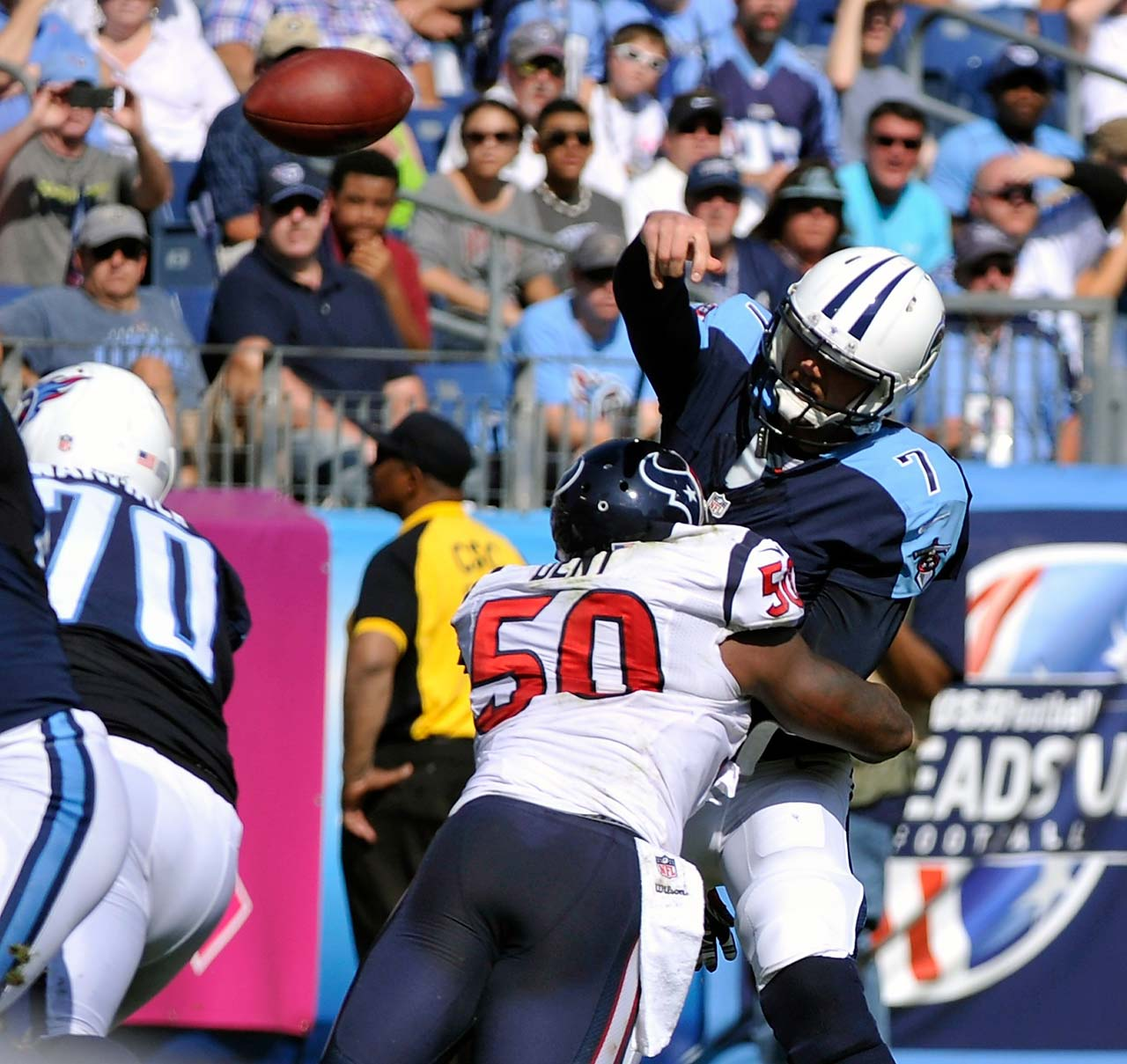 Rookie quarterback Zach Mettenberger of the Tennessee Titans is hit by Akeem Dent of the Houston Texans.