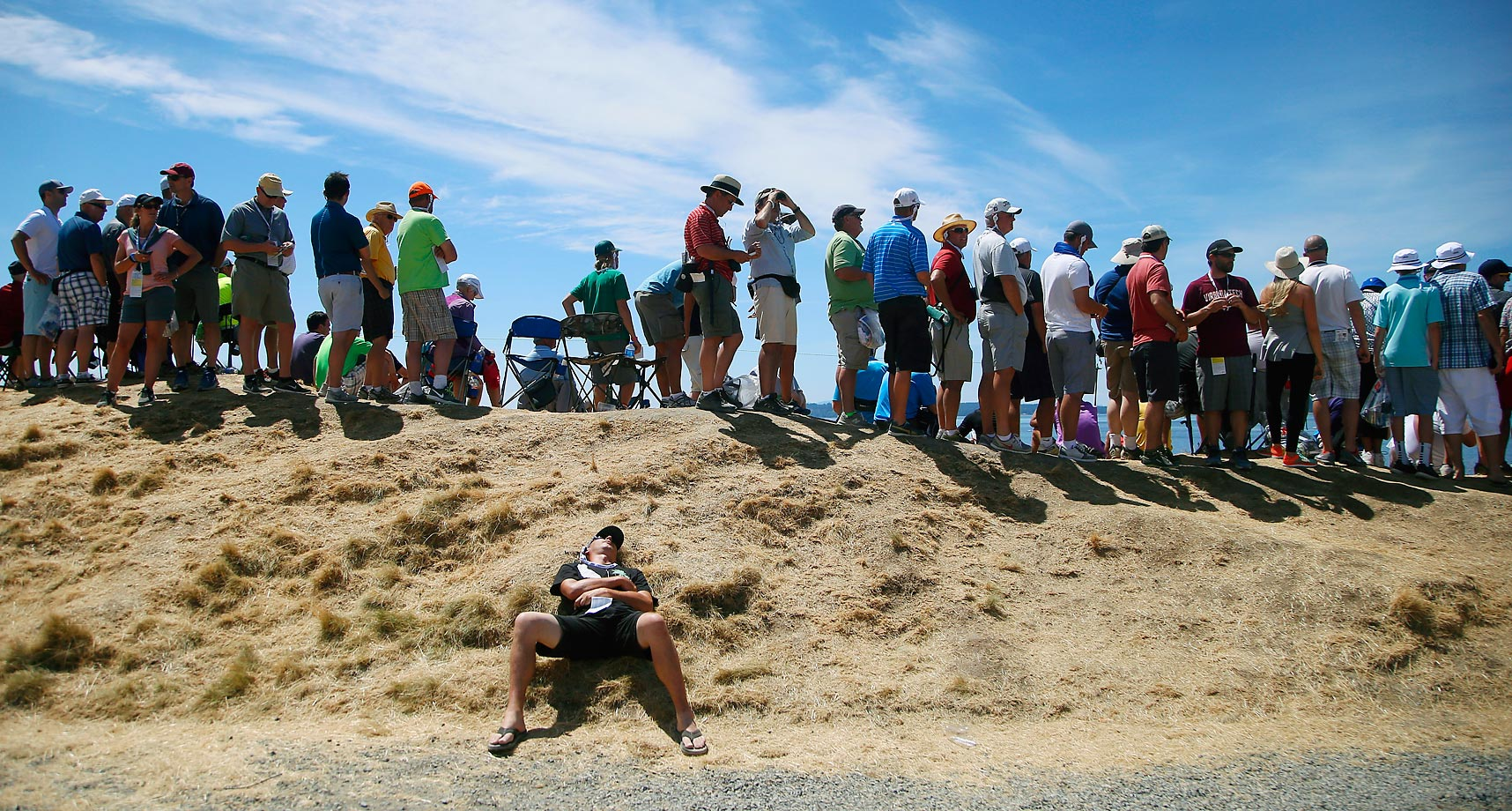 A fan takes a break near the second green during the final round of the U.S. Open.
