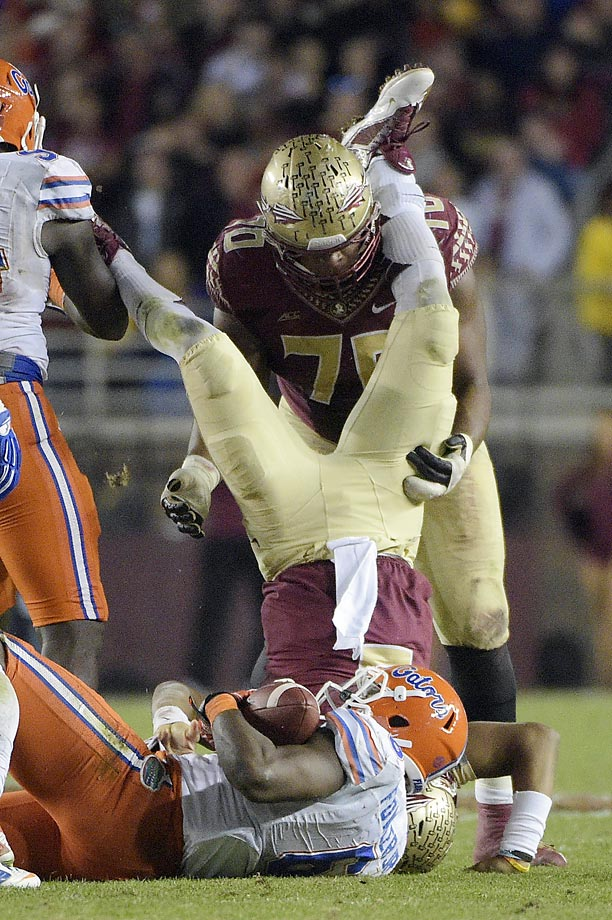 Florida State quarterback Jameis Winston is flipped over after being tackled by Florida's Dante Fowler, Jr.