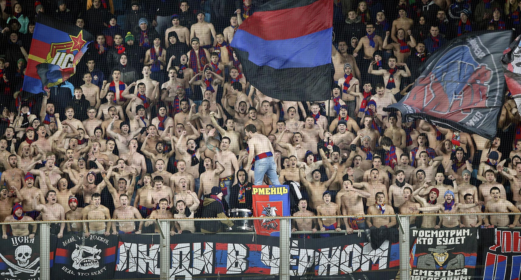 CSKA Moscow fans, most of them without their shirts on, cheer for their team in freezing temps during the Champions League Group B soccer match between CSKA Moscow and Manchester United.