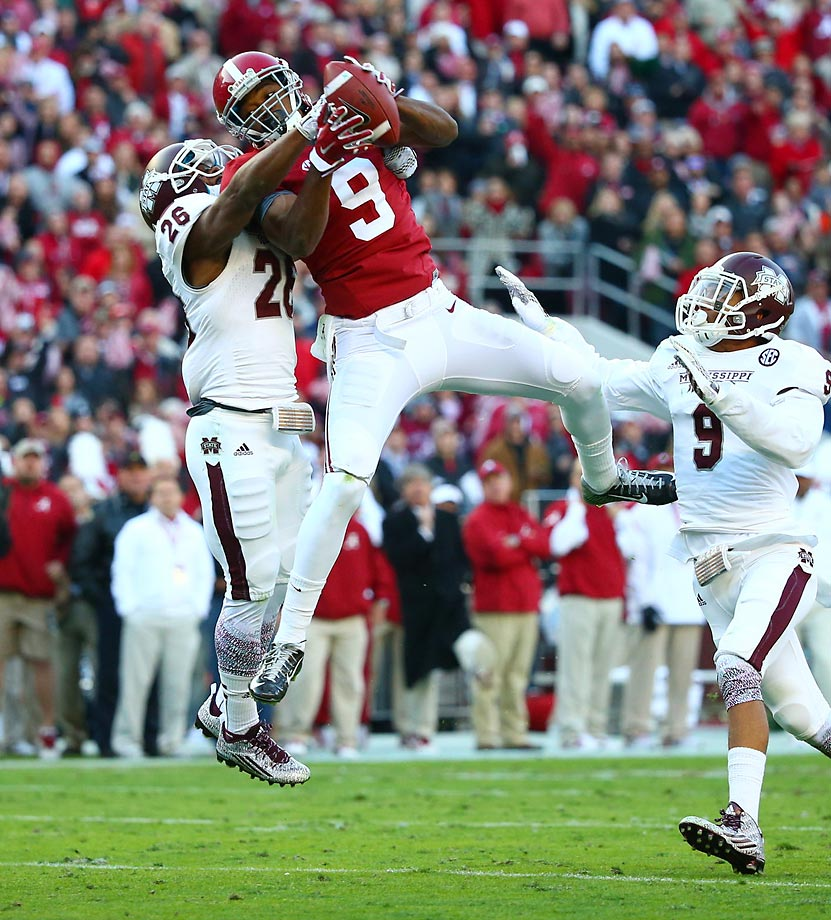 Alabama's Amari Cooper catches a 50-yard reception in the second quarter against Kendrick Market and Justin Cox of Mississippi State. The Crimson Tide handed the Bulldogs their first loss of the season, 25-20.