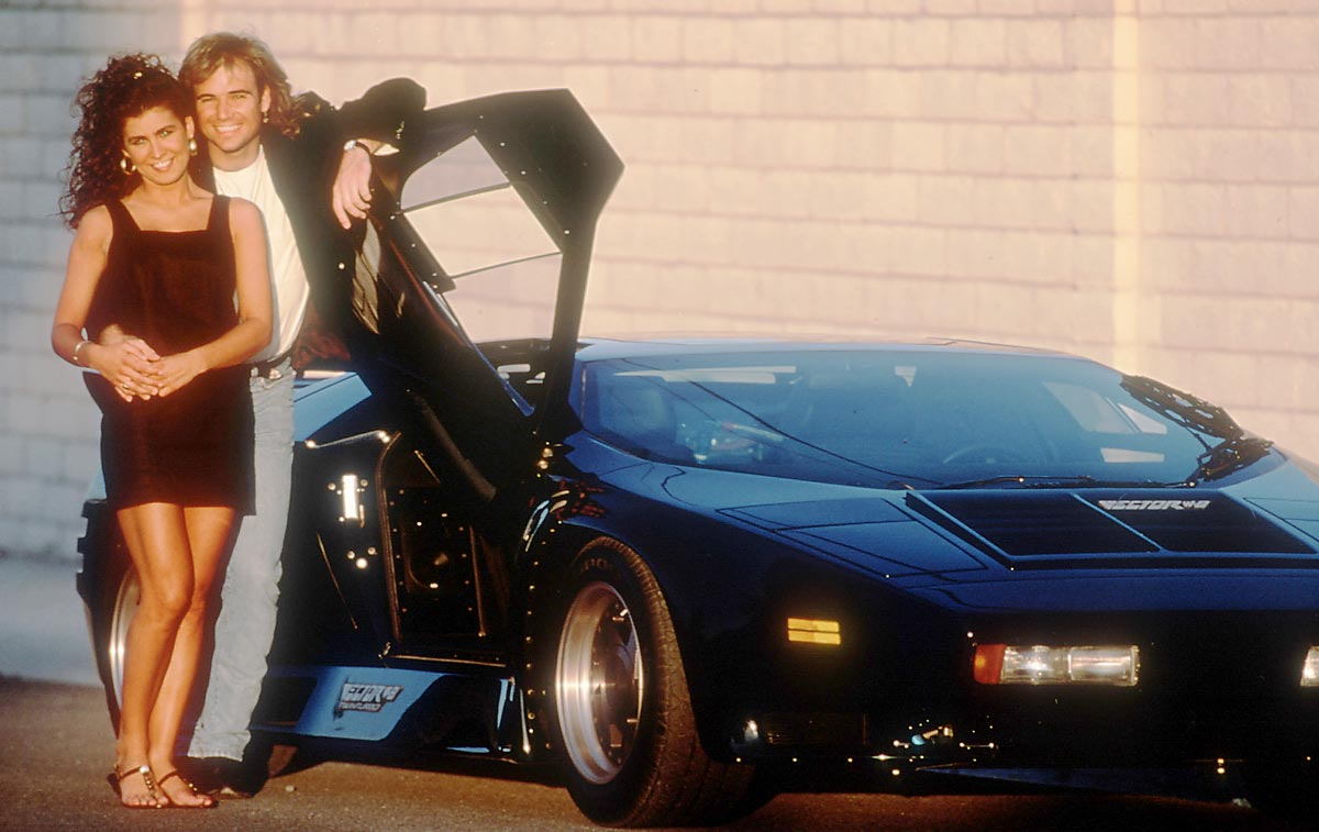 A young, long-haired Andre Agassi posing with his girlfriend, Wendi Stewart, next to his Vector W8 car.