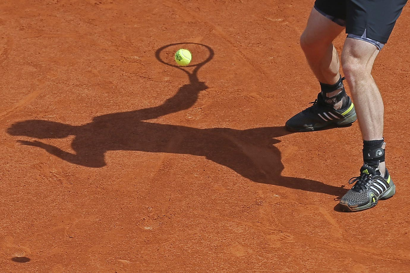 Shadows of Andy Murray at the French Open.  You can see his wedding ring attached to his left shoe.