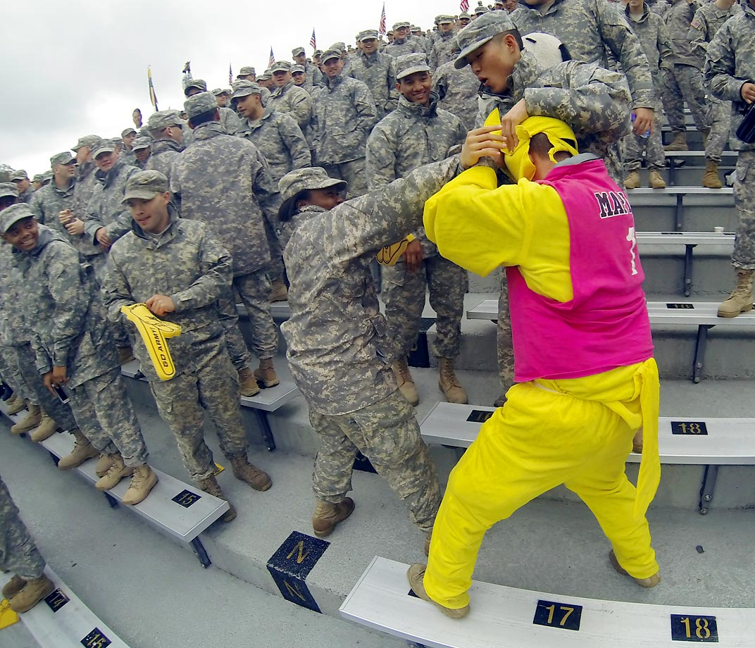 Army fans try to remove the mascot's head during a game against Rice.