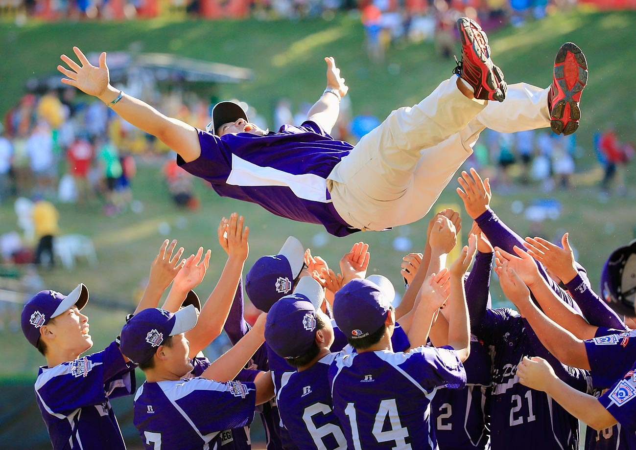 Seoul, representing the Asia-Pacific group, throws its assistant coach in the air after defeating the Great Lakes' Jackie Robinson West team from Chicago, 8-4, in the final game of the Little League World Series on August 24.