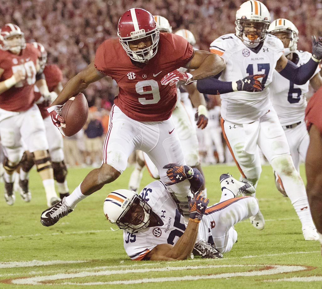 Auburn's Joe Turner attempts to bring down Alabama running back Amari Cooper in the 2014 Iron Bowl. Cooper finished with 224 yards in Alabama's 55-44 win.