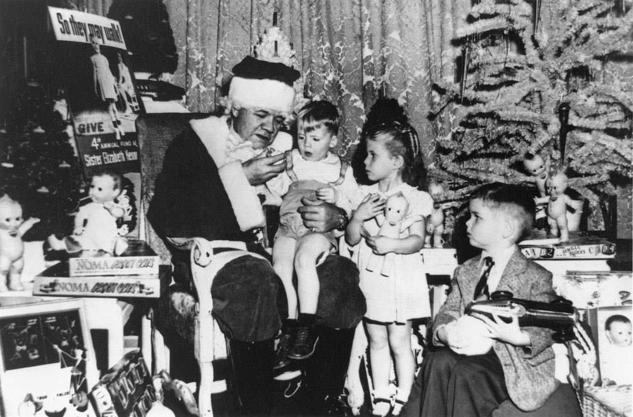 Babe Ruth, dressed as Santa Claus, sits with children during a Christmas Party for polio victims in Dec. 1947 at the Hotel Astor in New York City.