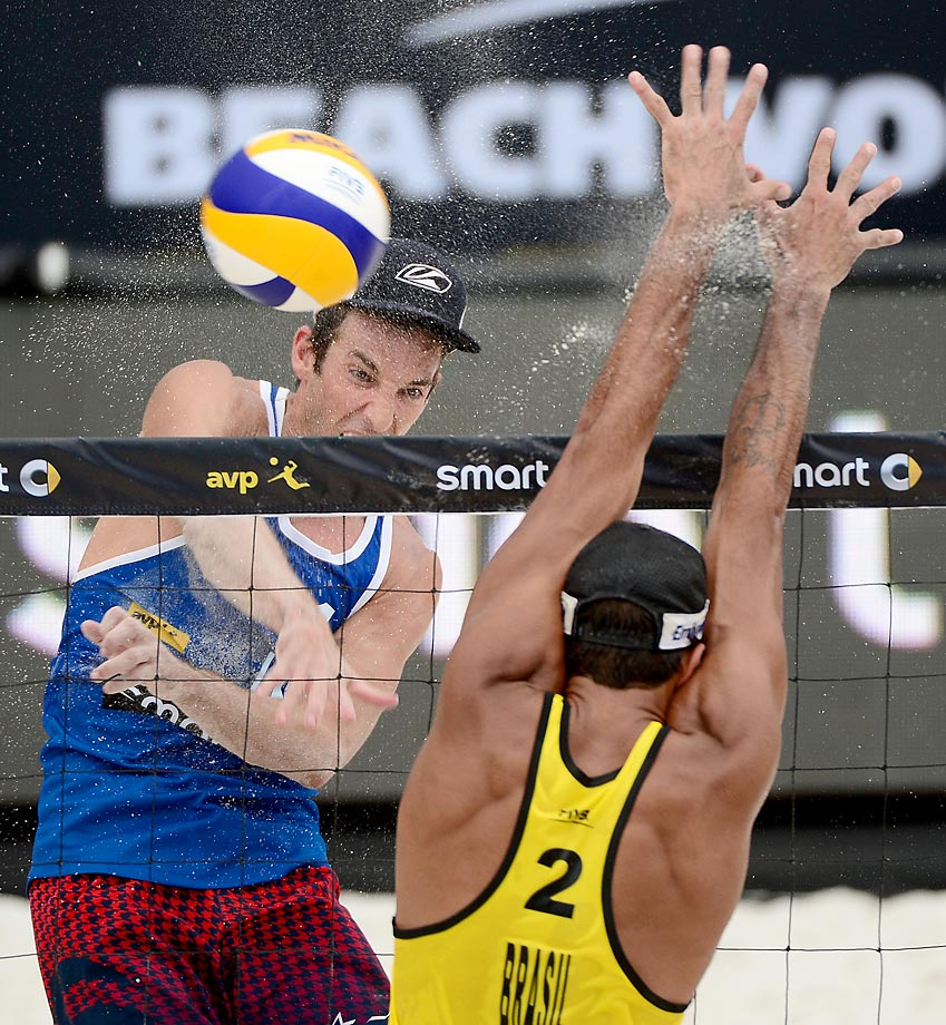 Nicholas Lucena of the U.S. spikes the ball against Pedro Solberg Salgado of Brazil.