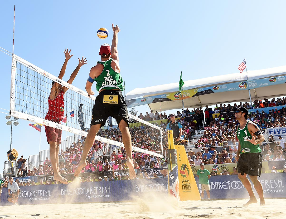 Alison Cerutti taps the ball over the arms of Phil Dalhausser. The Brazilians took the gold.