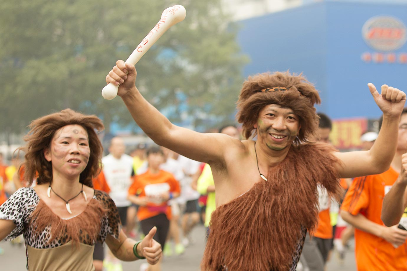"Two participants dressed as the figures in ""the Croods"" run in the 2014 Beijing International Marathon."