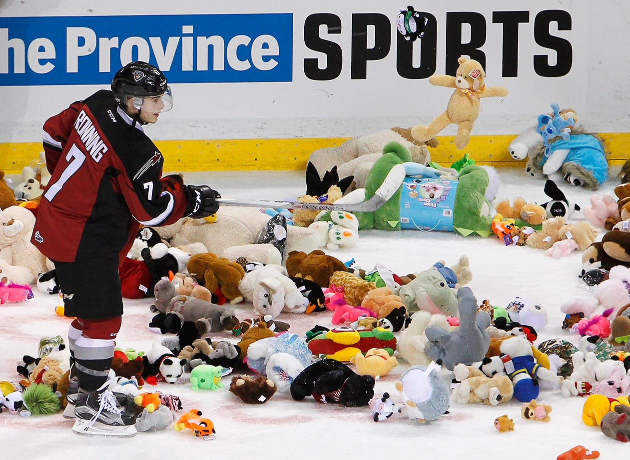 Ty Ronning of the Vancouver Giants helps pick up stuffed animals that were thrown on the ice after scoring a goal against the Everett Silvertips.