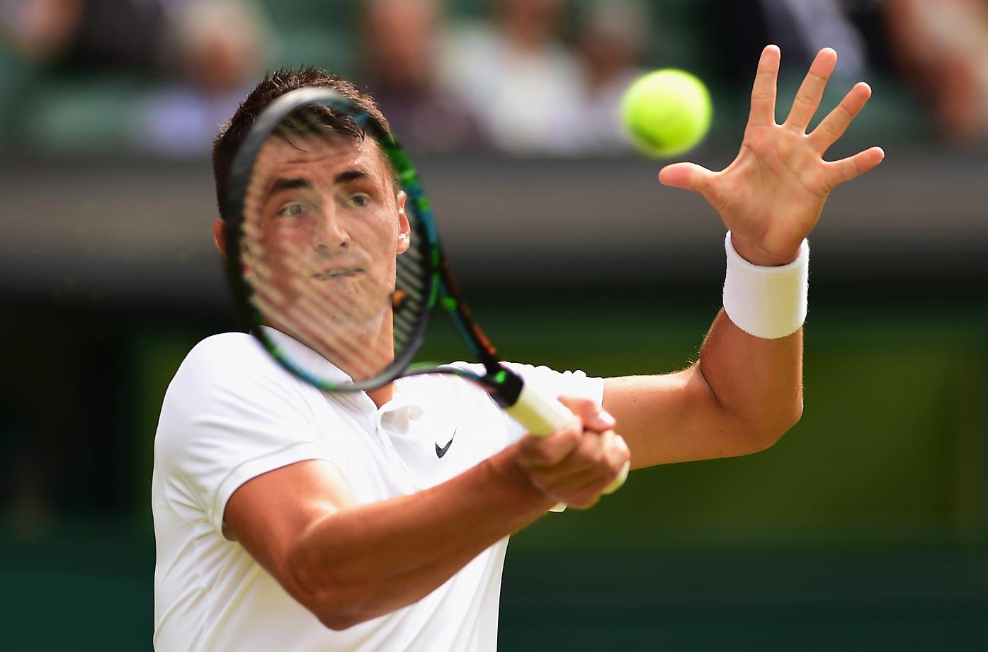Bernard Tomic plays a forehand against Novak Djokovic at Wimbledon.
