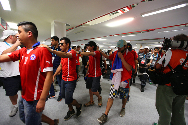 Chilean fans are led by Brazilian police and security personnel after breaking into Maracana Stadium before the start of their match against Spain.