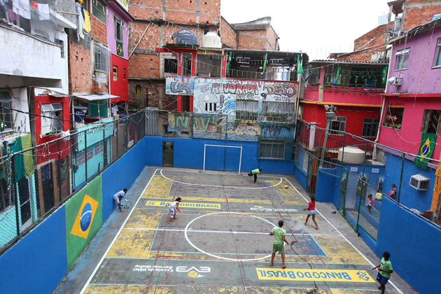 Local children playing soccer on the concrete pitch in the Tavares Basto Favela.