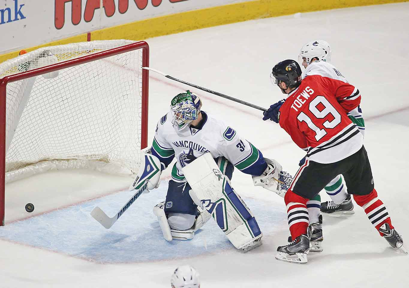 Jonathan Toews and Marcus Kruger score in the third period while Corey Crawford adds 15 saves in the frame for a total 36 on the night, out-dueling Eddie Lack in a 3-1 win over the Canucks in Chicago. The Blackhawks' 47th win of the season clinches a playoff spot for the seventh straight year.