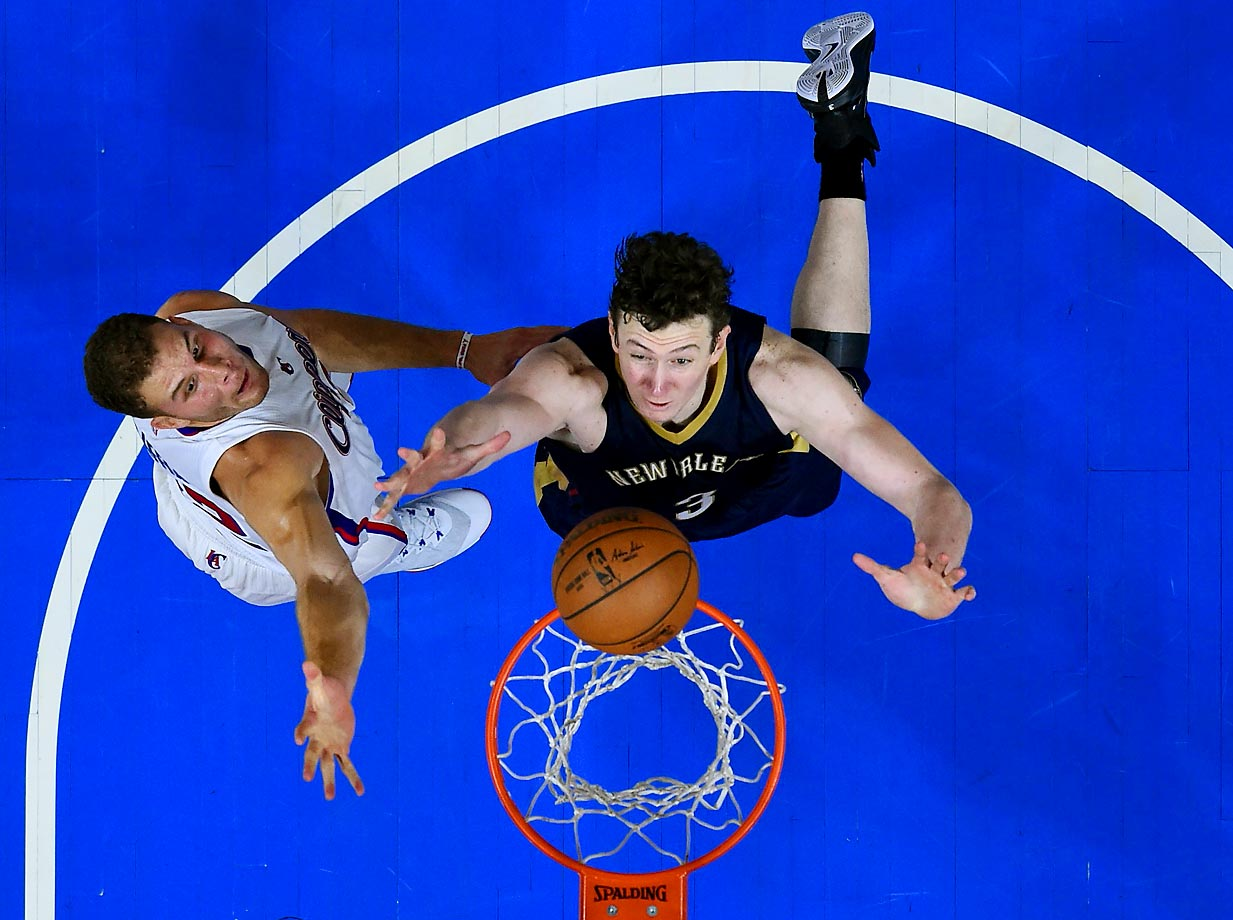 Blake Griffin of the Clippers tries to block a shot by Omer Asik of the Pelicans.