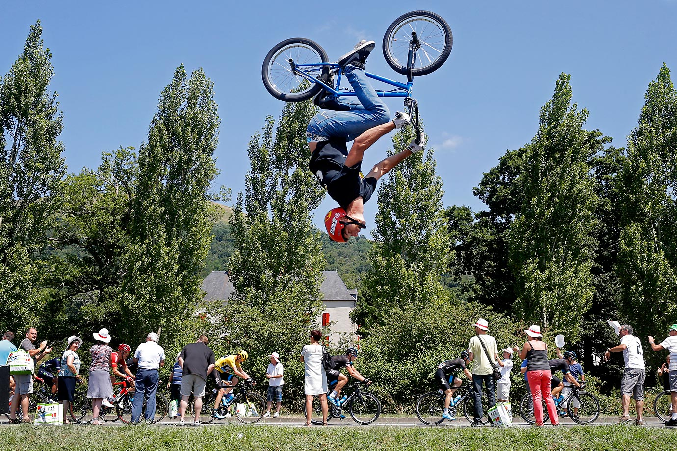 A BMX bike stunt as the pack of Tour de France riders pass by.