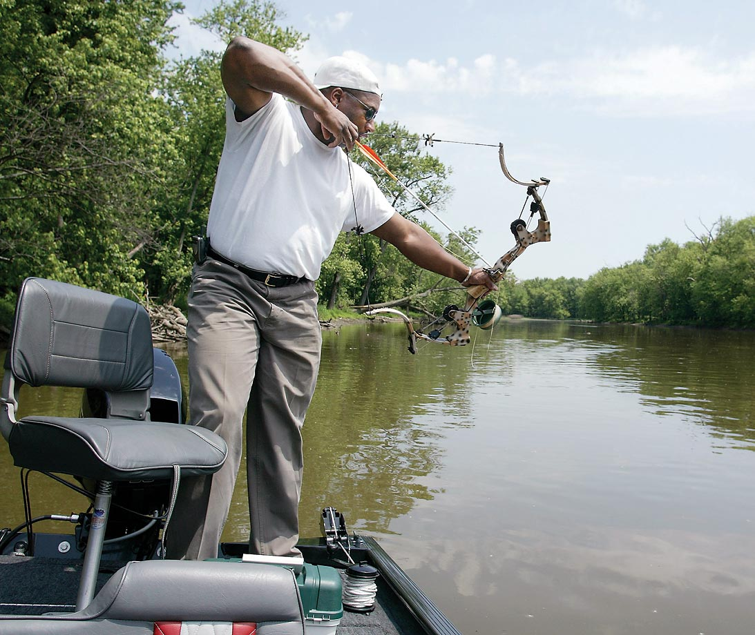 Bo Jackson on his boat on the Des Plaines River in Illinois, spearing fish with a cross-bow in 2003.