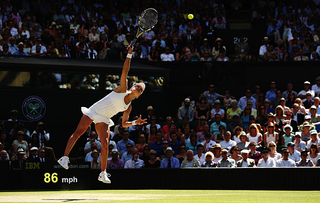 Eugenie Bouchard serves against Simona Halep in the Wimbledon semifinals.