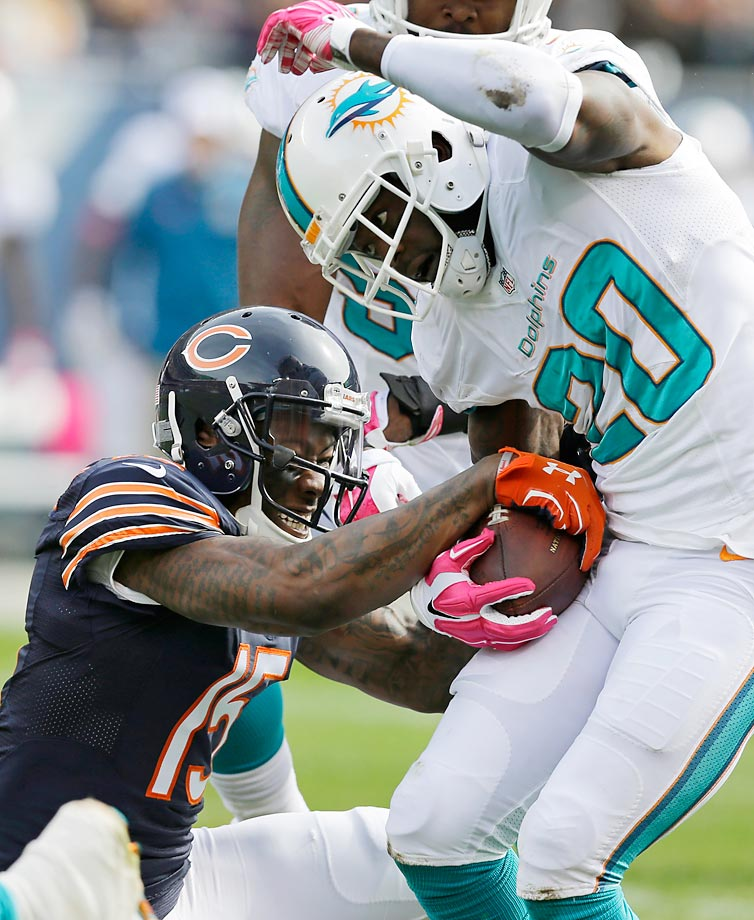 Chicago Bears wide receiver Brandon Marshall tries to strip the ball from Miami Dolphins safety Reshad Jones after Jones intercepted a pass.