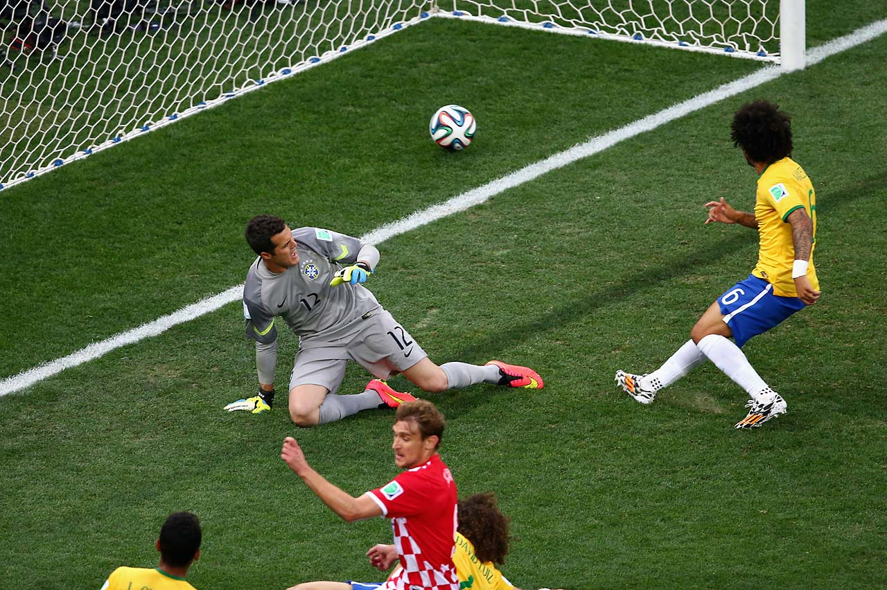 Julio Cesar (left) and Marcelo of Brazil watch as a deflected shot goes in.