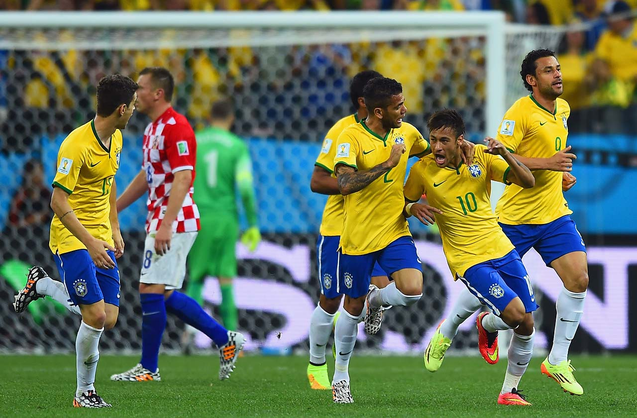 Neymar celebrates with Dani Alves and Fred after a goal in the first half.