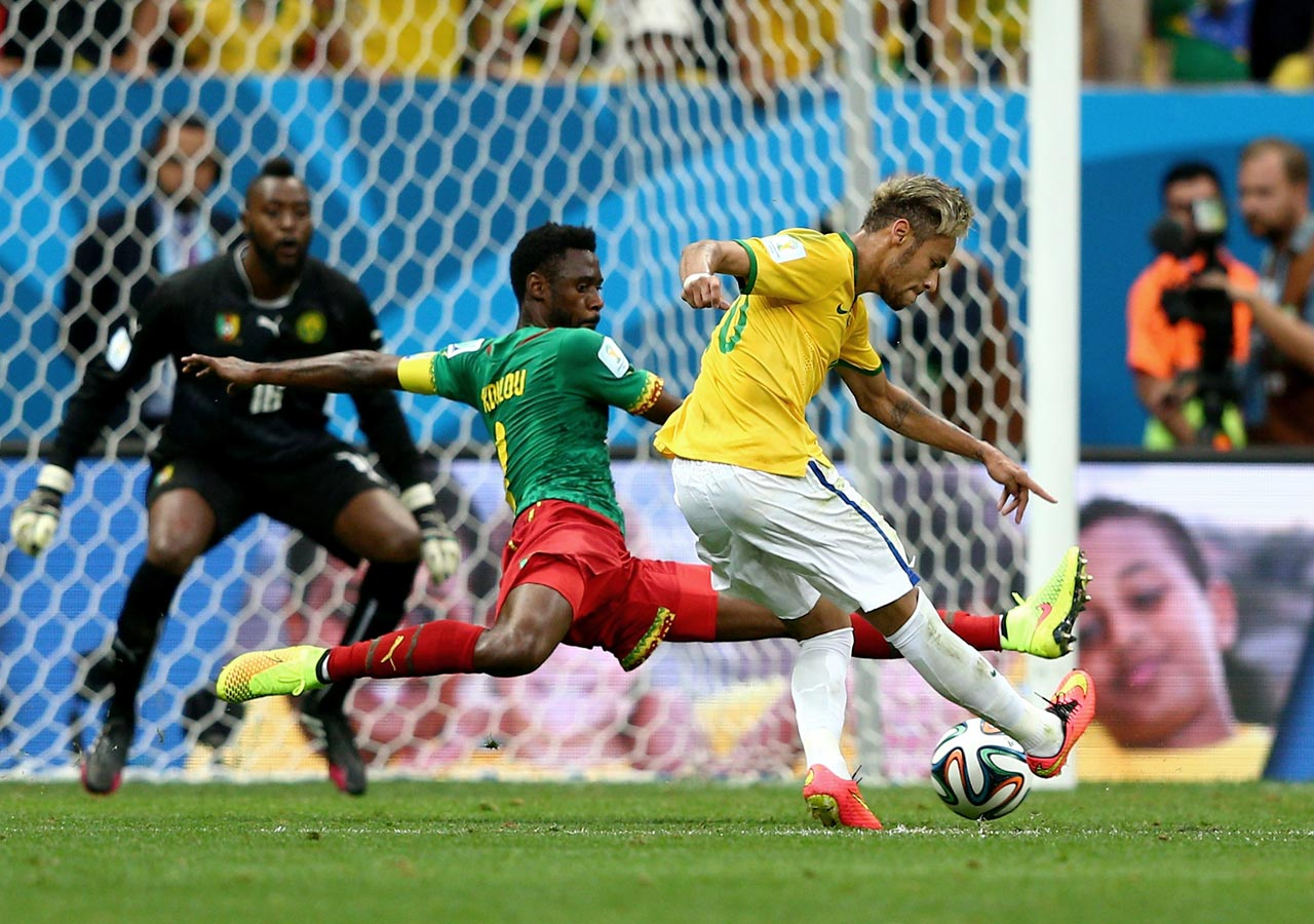 Neymar slides a shot under Cameroon defender Nicolas N'Koulou to score in Brazil's 4-1 win, which secured first place in Group A.