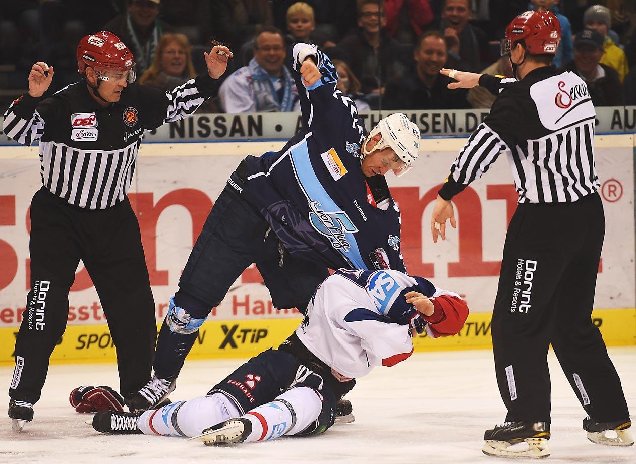 Bretton Stamler of Hamburg fights with Dominik Bittner of Mannheim during the DEL ice hockey match bewteen the Hamburg Freezers and Adler Mannheim in Hamburg, Germany.