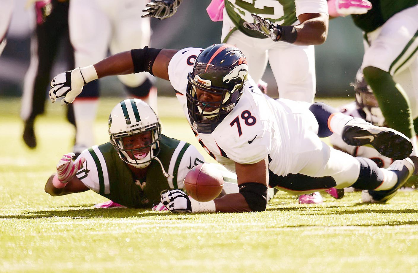 New York Jets defensive back Darrin Walls and                    Denver Broncos offensive tackle Ryan Clady scramble for a loose ball.