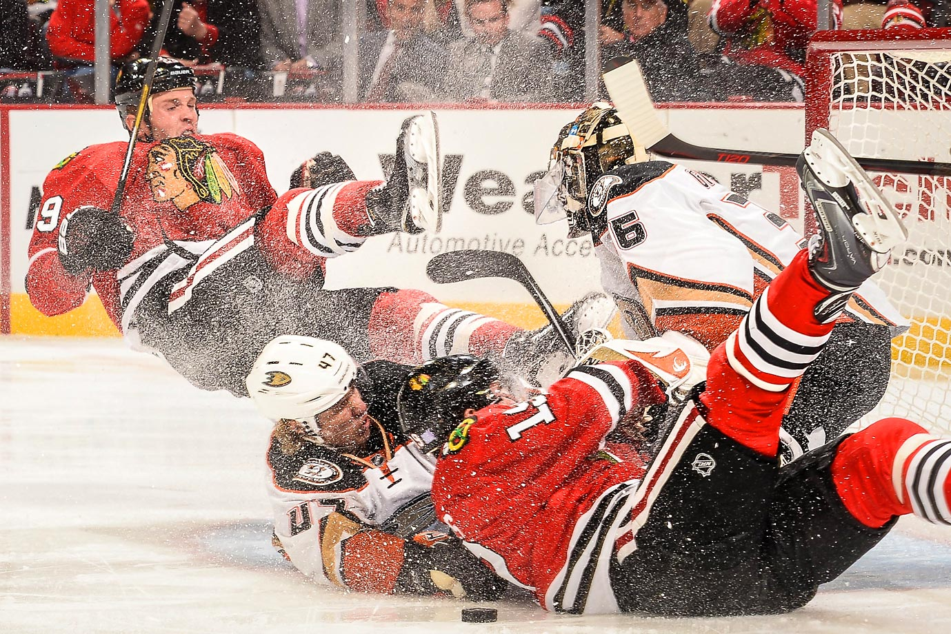 The Blackhawks' Bryan Bickell and Jonathan Toews and the Ducks' Hampus Lindholm collide with Anaheim goaltender John Gibson.