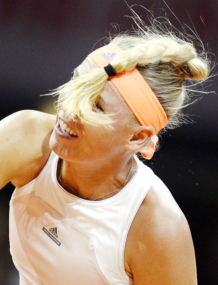 Caroline Wozniacki's hair flips into her face during a serve at the semifinals of the WTA Porsche Tennis Grand Prix.