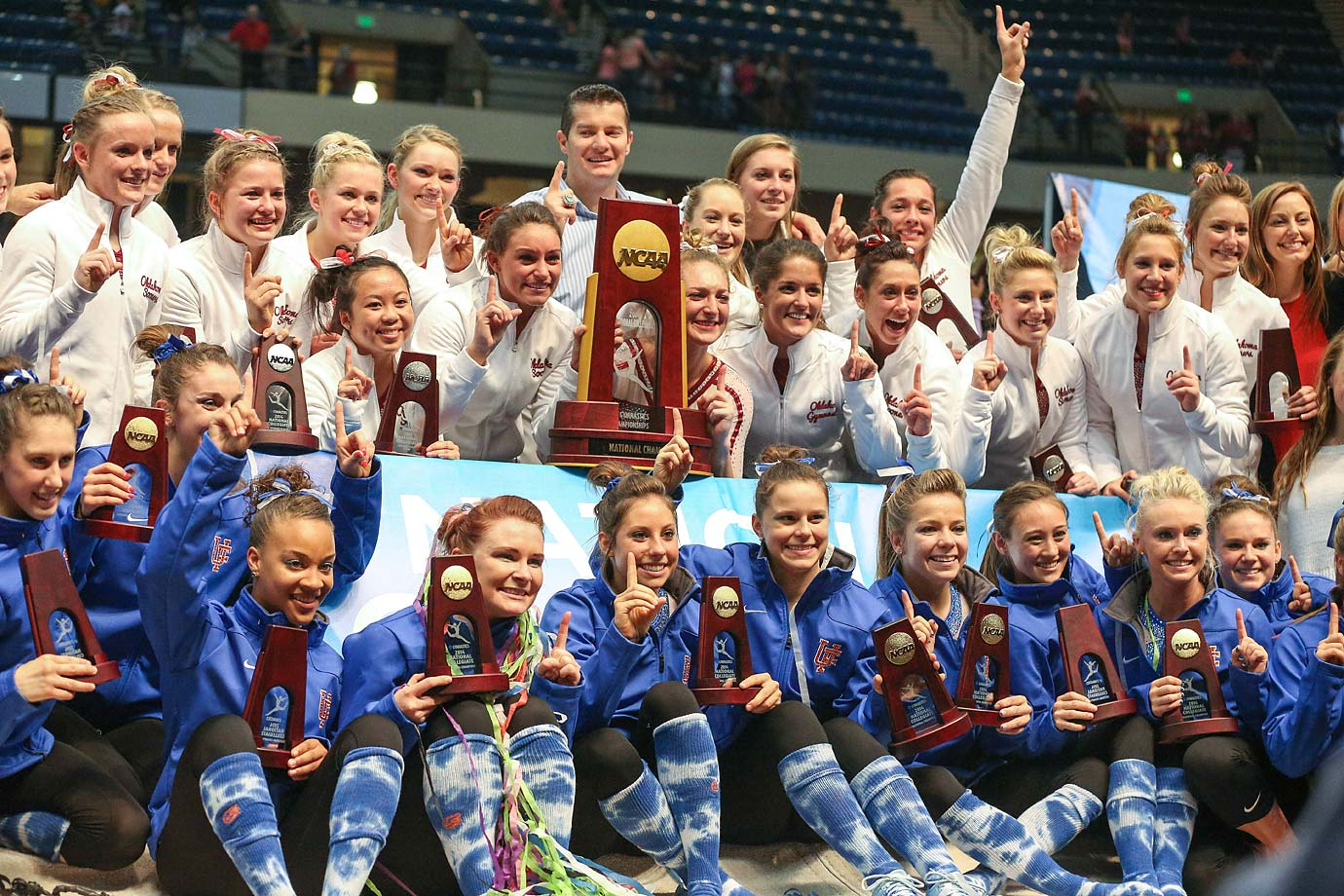 The members of Oklahoma and Florida's women's gymnastics teams pose together after being declared co-champions, the first time that's happened in the sport's collegiate history.