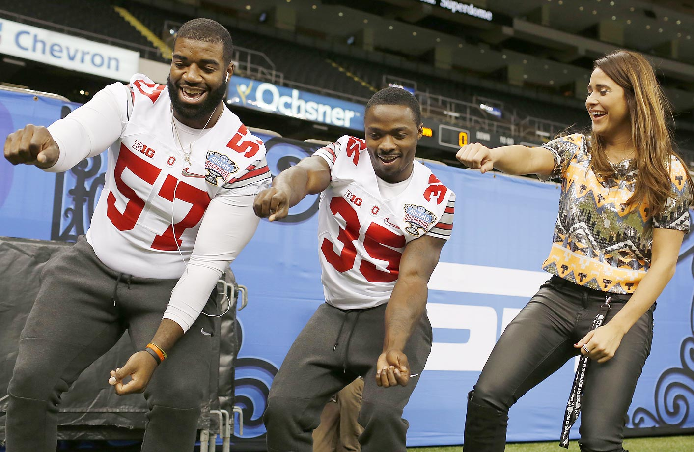 "Ohio State's Chase Farris (left) and Jeffie Johnson dance  with Rayven Tirado of ESPNU's  ""Road Trip"" during media day for the Sugar Bowl."