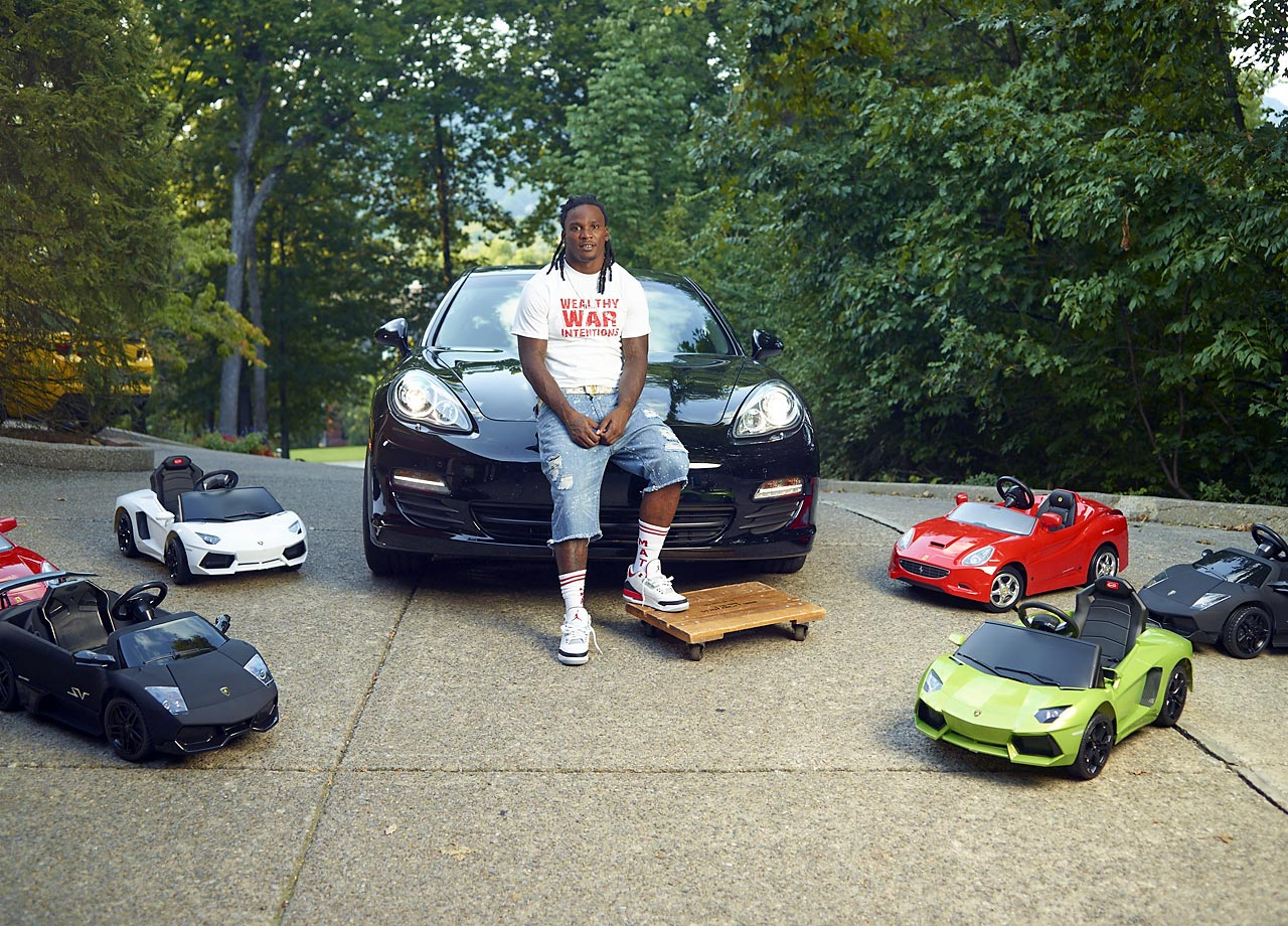 Running back Chris Johnson sitting on the hood of his black vehicle, with a bunch of toy sports cars around his feet.