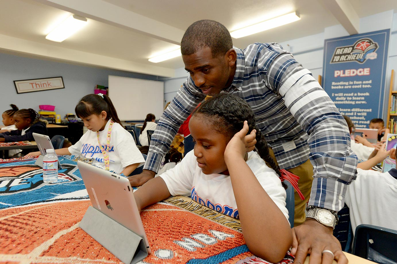 Chris Paul of the Los Angeles Clippers works with a child at the Salvation Army Seimon Family Youth and Community Center before unveiling a renovation of the Read To Achieve Learn and Play Center by the Los Angeles Clippers Foundation and the CP3 Foundation.