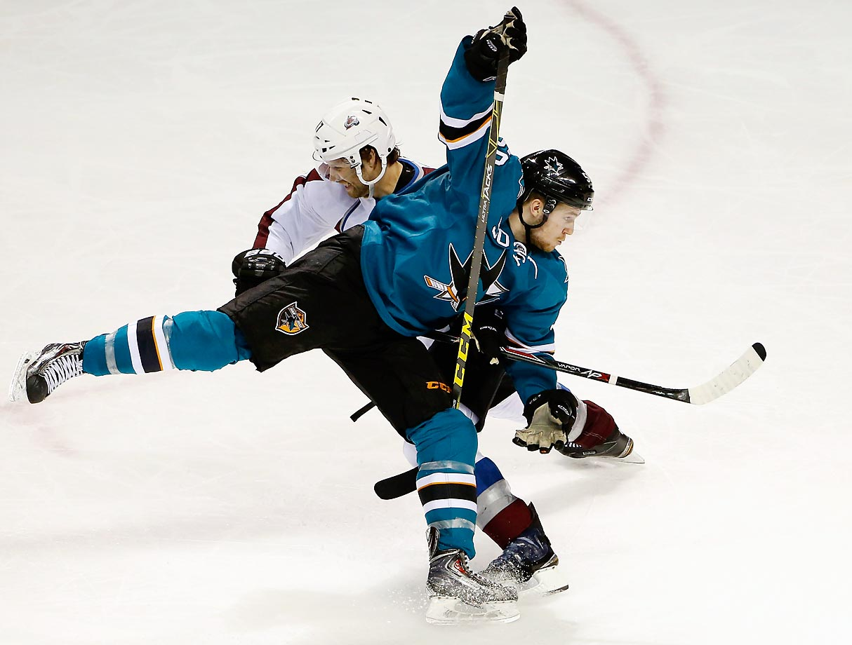 Chris Tierney of the San Jose Sharks gets tangled with Brad Stuart of the Colorado Avalanche.