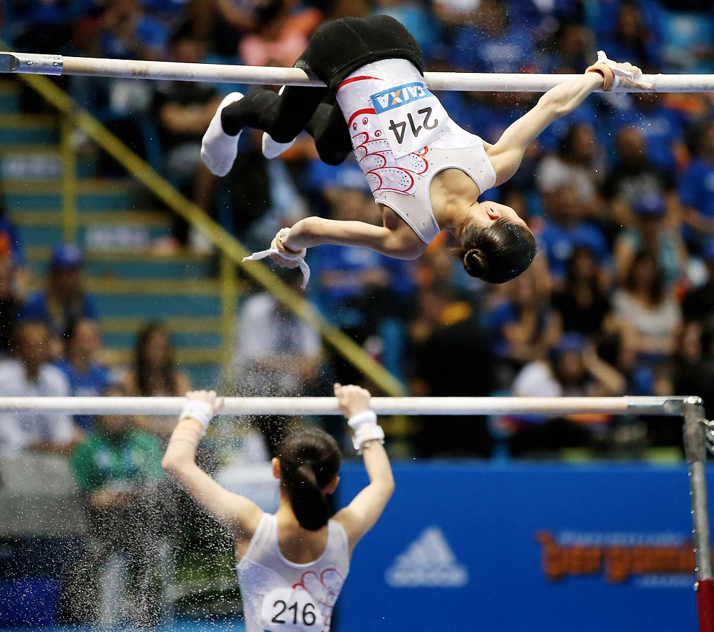 Chunsong Shang and Siyi Chen of China prepare the Uneven Bars before competition.