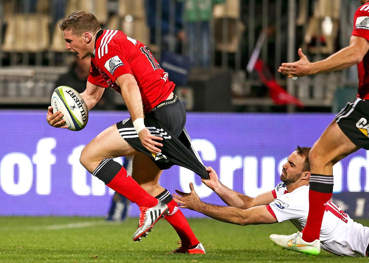 During a Super Rugby match in Christchurch, New Zealand, Nick Frisby, of the Queensland Reds, attempts to tackle Colin Slade, of the hometown Crusaders.