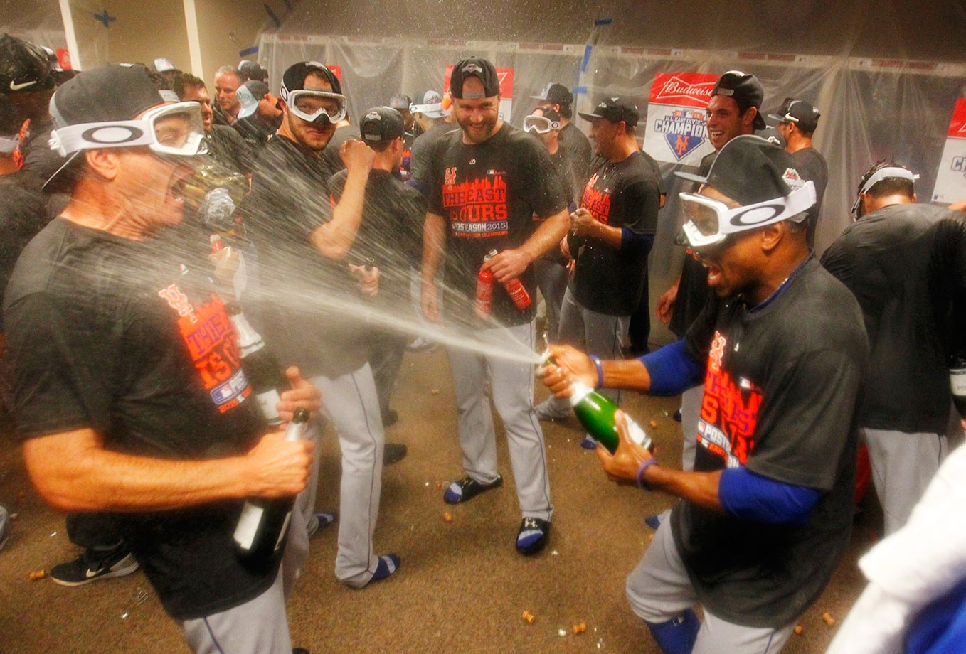 Curtis Granderson of the New York Mets sprays champagne on Bob Geren as they celebrate clinching the National League East.