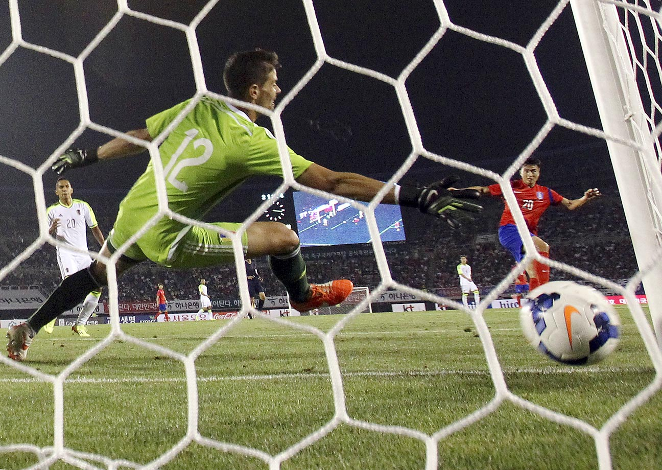 Venezuela's goal keeper Daniel Hernandez fails to block a goal by South Korea's Lee Dong-gook during the friendly in Bucheon, South Korea.  South Korea defeated Venezuela 3-1.