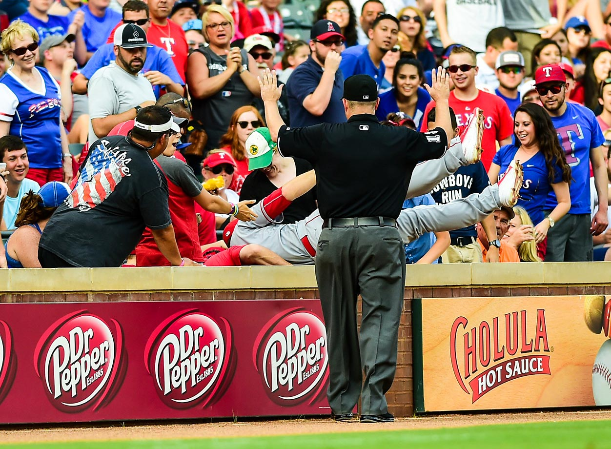David Freese of the Los Angeles Angels dives over the wall in a game against the Rangers.