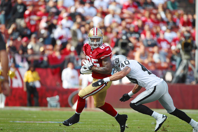 Vernon Davis uses his strength to shed tacklers and looks for running room after making a catch against the Oakland Raiders.